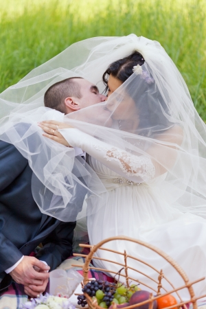 groom and the bride together sit on a grass with a big basket of fruit and kiss