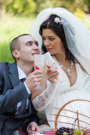 groom and the bride together sit on a grass with champagne glasses in hands photo