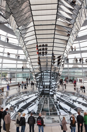 BERLIN, GERMANY - SEPTEMBER 24:Tourists under  Reichstag dome, September 24, 2012, Berlin, Germany. After moving of the Bundestag to Berlin in 1999 the building of the Reichstag was visited by over 13 million people from all over the world: