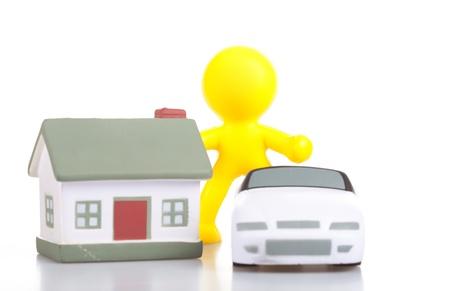 the little man: Un piccolo uomo sorridente costi giocattolo vicino alla casa e la macchina. Il concetto di acquisto di beni immobili. Archivio Fotografico