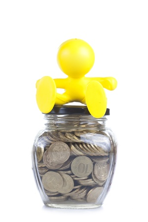 little yellow man sits on a glass jar with gold coins. Symbol of accumulation of money Stock Photo - 16660505