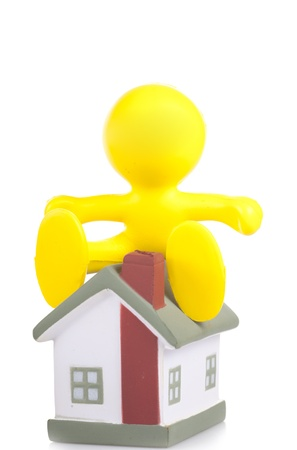 yellow little man sits on a house roof Stock Photo - 16660501