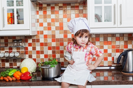 girl in a cook cap with a ladle in a hand sits on a kitchen table photo