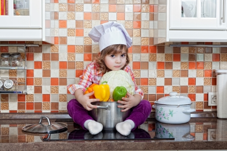 girl cook with fresh vegetables sits on a kitchen table photo