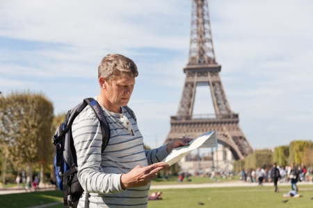 man - the traveler near the Eiffel Tower looks in a map of the city photo