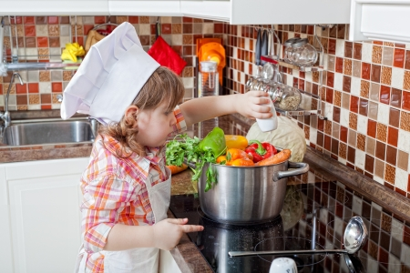 little girl plays the cook and makes a dinner photo