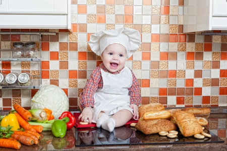 Baby cook with bread and steering-wheels sits on a kitchen table photo