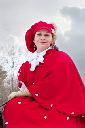woman in red riding habit sits astride the Oryol trotter photo