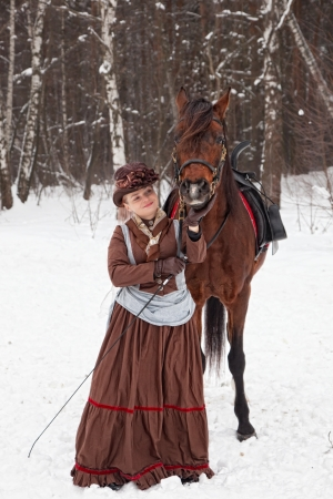 woman keeps the Arab racer in the brown riding habit photo