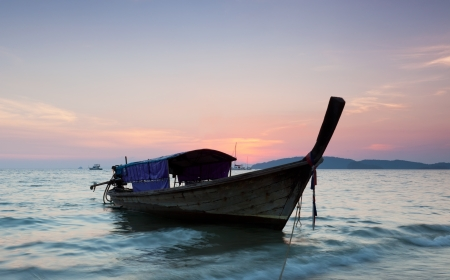 Longtail against a sunset. Thailand. photo