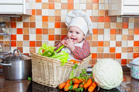 Child sits in a wattled basket on a table with vegetables photo