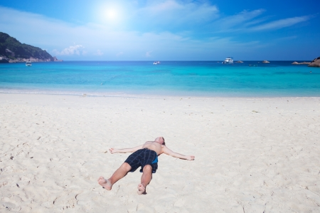 Man lies on a beach on an ocean coast photo