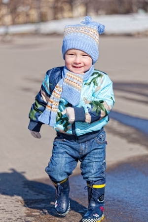 Little boy goes on a pool in rubber boots photo