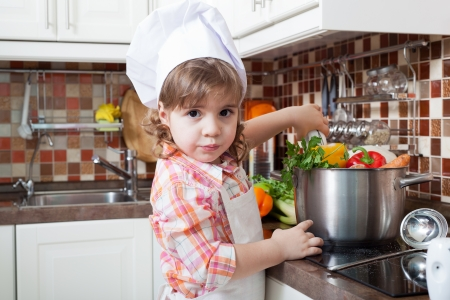 helps: Little girl plays the cook and makes a dinner Stock Photo