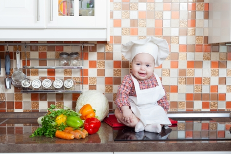 Baby cook with vegetables sits on a kitchen table photo