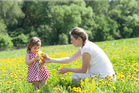 Mother with the small daughter play on a glade with dandelions photo