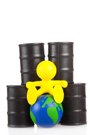 the little man: giocattolo piccolo uomo si siede accanto a mozziconi al petrolio del globo. Il concetto di supremazia mondiale di petrolio l'estrazione delle aziende Archivio Fotografico