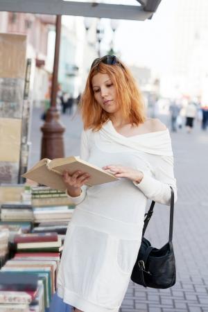 selects: ragazza sceglie il libro da negozio stradale