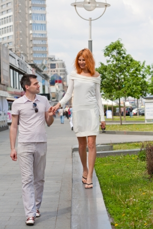 Young loving couple walks in the summer around the city photo