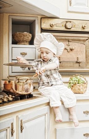 aliments droles: petit gar�on est assis sur une table de cuisine et joue le cuisinier Banque d'images