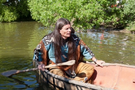 North American Indian floats down the river on a canoe photo