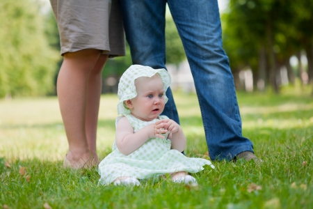 Cheerful baby girl is playing on the grass photo