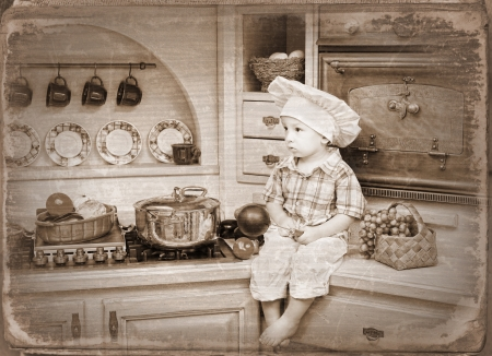 little boy sits on a kitchen table and plays the cook Stock Photo - 22646461