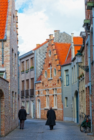 Two persons go on the old street to Bruges, the wall has a bicycle photo