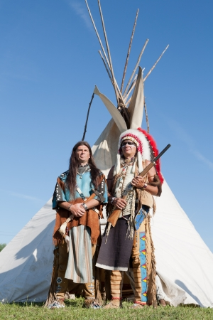 swarty: Two North American Indians stand near a wigwam