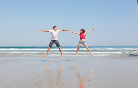 young loving couple joyfully jumps on a tropical beach photo