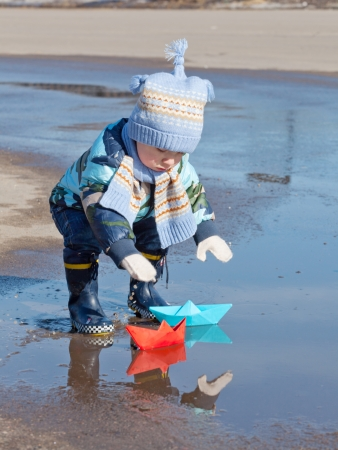 muddy clothes: Little boy plays with paper ships in a puddle Stock Photo