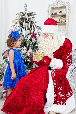 nicolas: Saint Nicolas gives Christmas gifts to the little girl