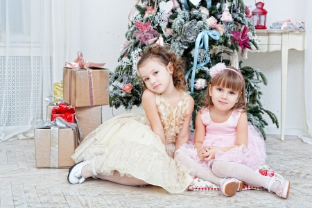 Two girls sit  near a Christmas fir-tree photo