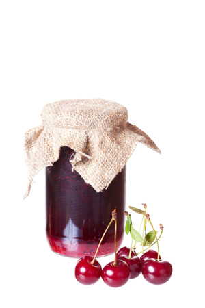 ripe cherries and a glass jar with cherry jam photo