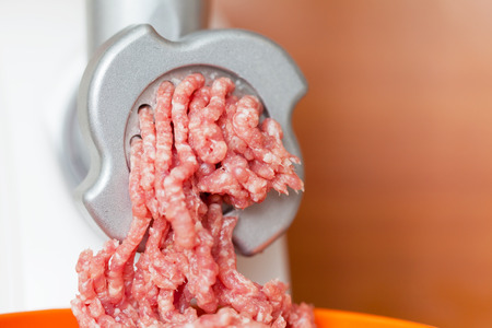 Closeup of minced meat coming out from grinder in shop  photo