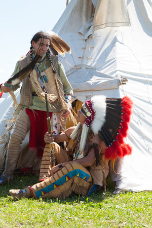 Two North American Indians communicate near a wigwam photo