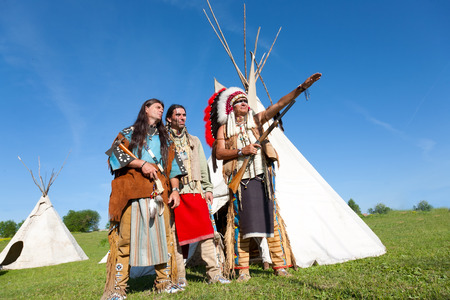red skinned: Three North American Indians stand near a wigwam