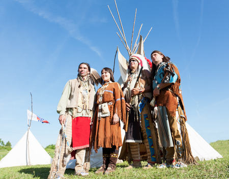 Four North American Indians of a tribe of Lakot stand at a wigwam photo