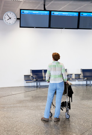 attentively: Woman at the airport attentively looks at an information display