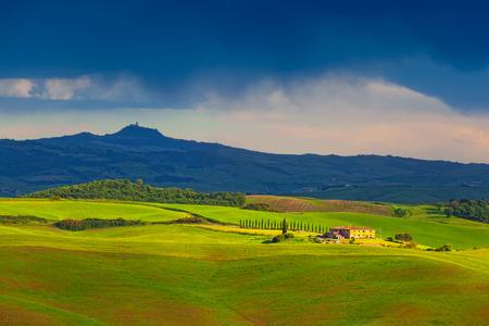 thundercloud: I campi e le colline della Toscana brillato con il sole del tramonto da sotto una nube temporalesca