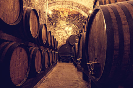 Wooden barrels with wine in a wine vault, Italy photo