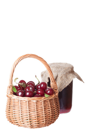 Ripe cherry in a wattled basket and bank of cherry jam photo