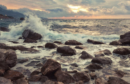 inflow: Waves break with splashes about big stones at sunrise, the Crimea