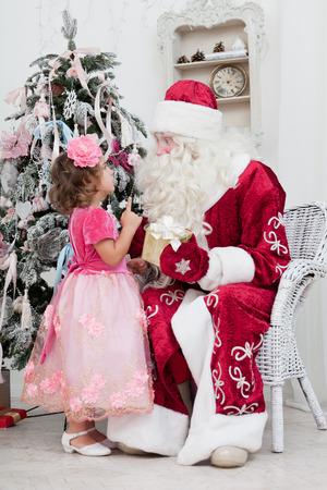 conversaciones: La ni�a habla a Santa Claus cerca de un abeto de Navidad