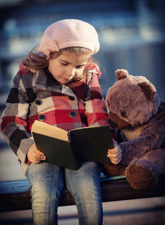 vignetting: Little girl reads the book to a toy bear, toning, vignetting Stock Photo