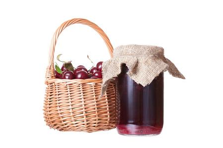 Bank with cherry jam and a basket with ripe cherries photo