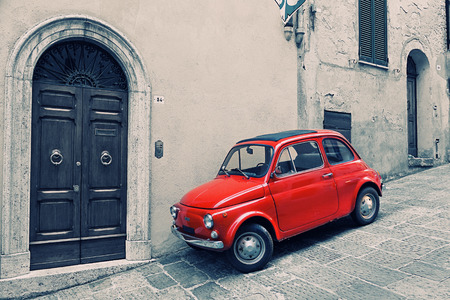 ITALY, MONTEPULCHANO - MAY 16, 2014: Old red Fiat 500 R to stand near a wall. Fiat Nuova 500 (ital. cinquecento) — the car made by the Fiat company with 1957 on 1975