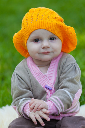 green beret: Little girl in an orange beret against a green grass Stock Photo