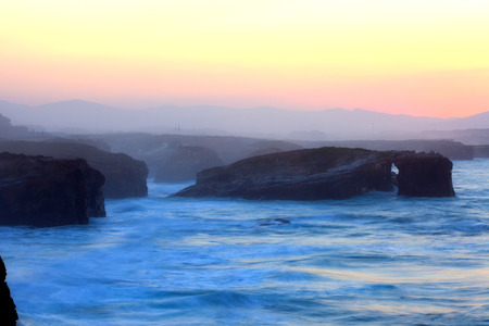 inflow: Beautiful sunset and stone arches on Playa de las Catedrales during inflow, Spain