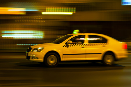 panning shot: yellow taxi moves on the night city street